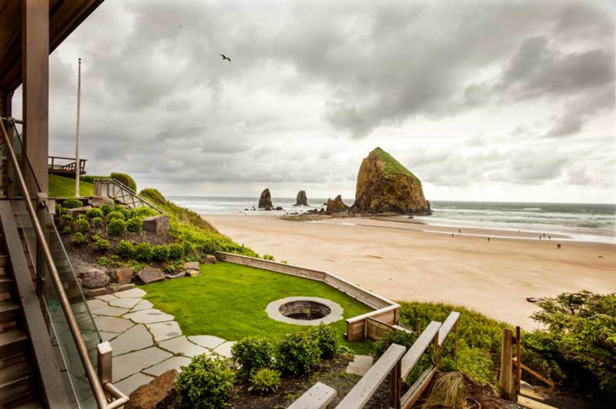 The cozy cottage on Cannon Beach has a great view of Haystack Rock. New landscaping with a firepit takes advantage of a cliff edge protected from the wind.