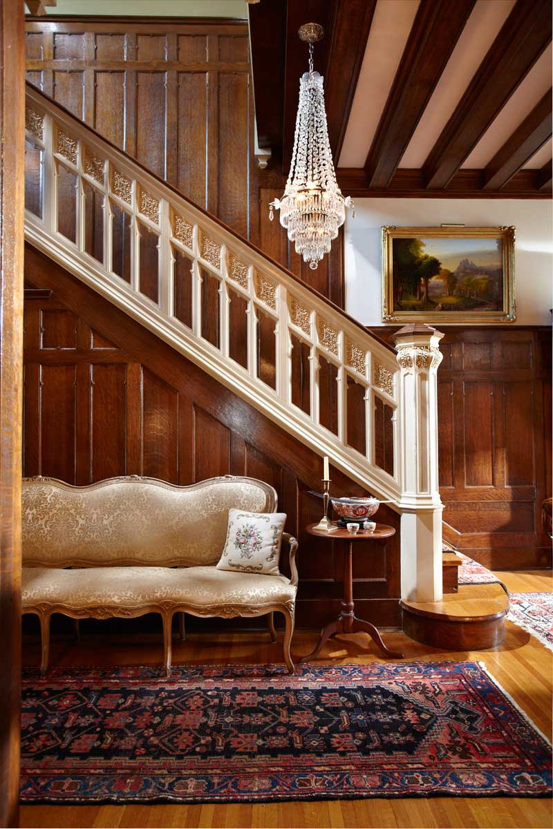 The Tudor–Gothic stair hall features a painted balustrade with Gothic details against a backdrop of carved oak board-and-batten wainscoting. A Louis XV settee adds curvy elegance.