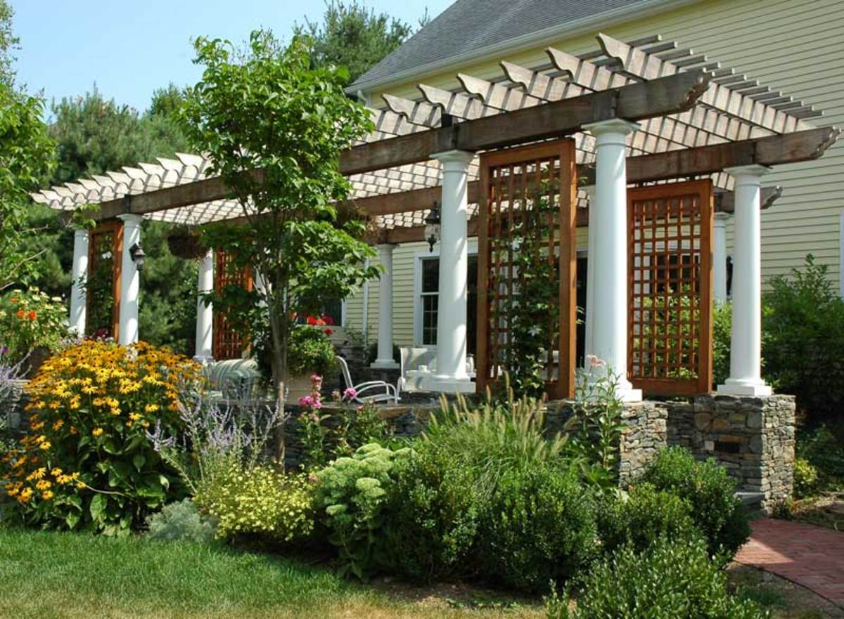 The pergola with classical columns on stone bases is by FineHouse, Ltd.