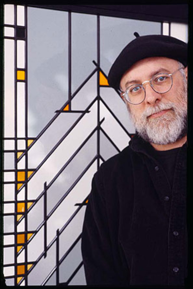 Arthur Stern in front of a glass-paneled room screen.