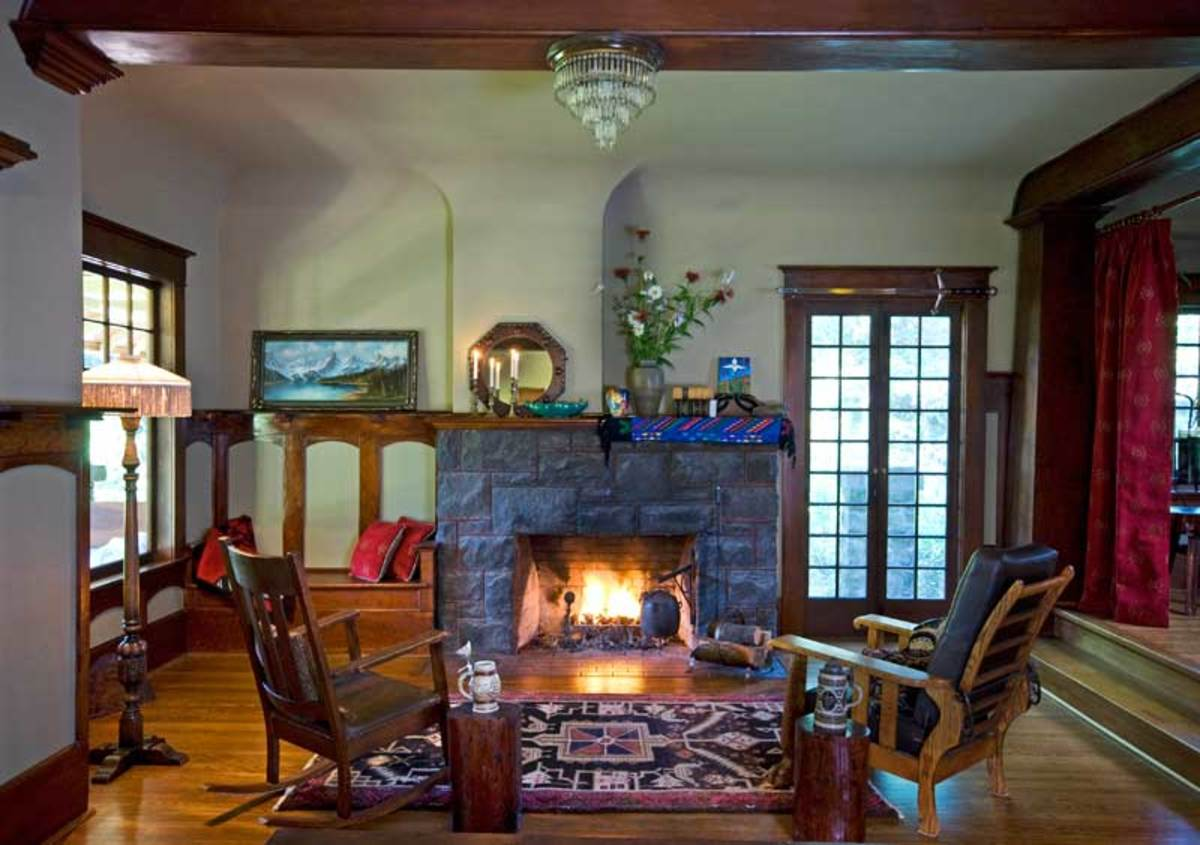 Woodwork, the coved ceiling, and a substantial stone fireplace, all original, lend period styling to the living room.
