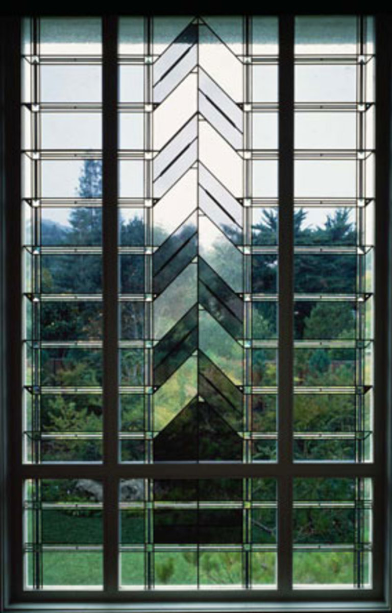 A landing window with clear and tinted glass and beveled prisms.