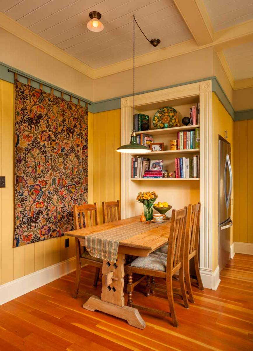 The shelving recess provides tuck-in space for the long Danish trestle table.  The tapestry incorporates and inspired the room's color palette.