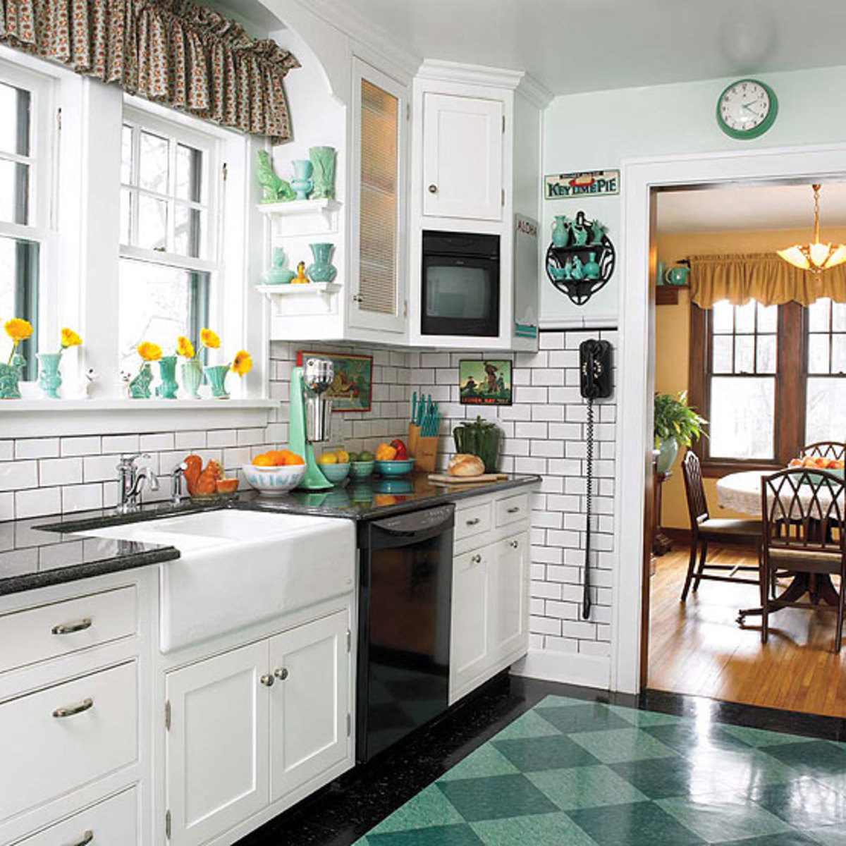 Dark gray grout makes the subway tile pop and plays off the polished granite counters. Every detail was carefully chosen, from the dial telephone to the vintage Oster milkshake blender.