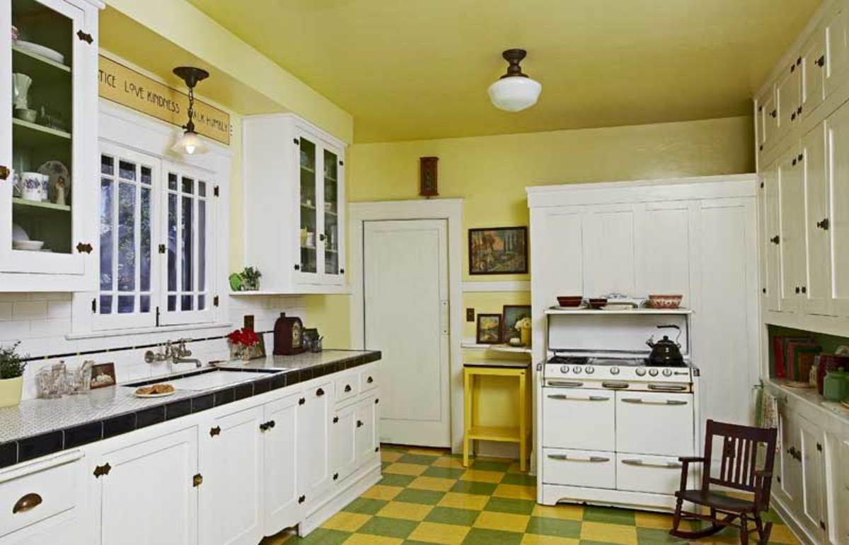 The long wall retains original cabinets. Commercial vinyl tile approximates period linoleum on the floor.