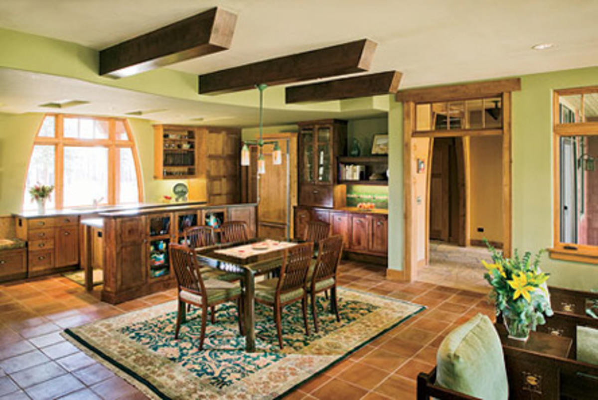 A curved dropped ceiling defines the kitchen, which is separated from the dining area by an island.
