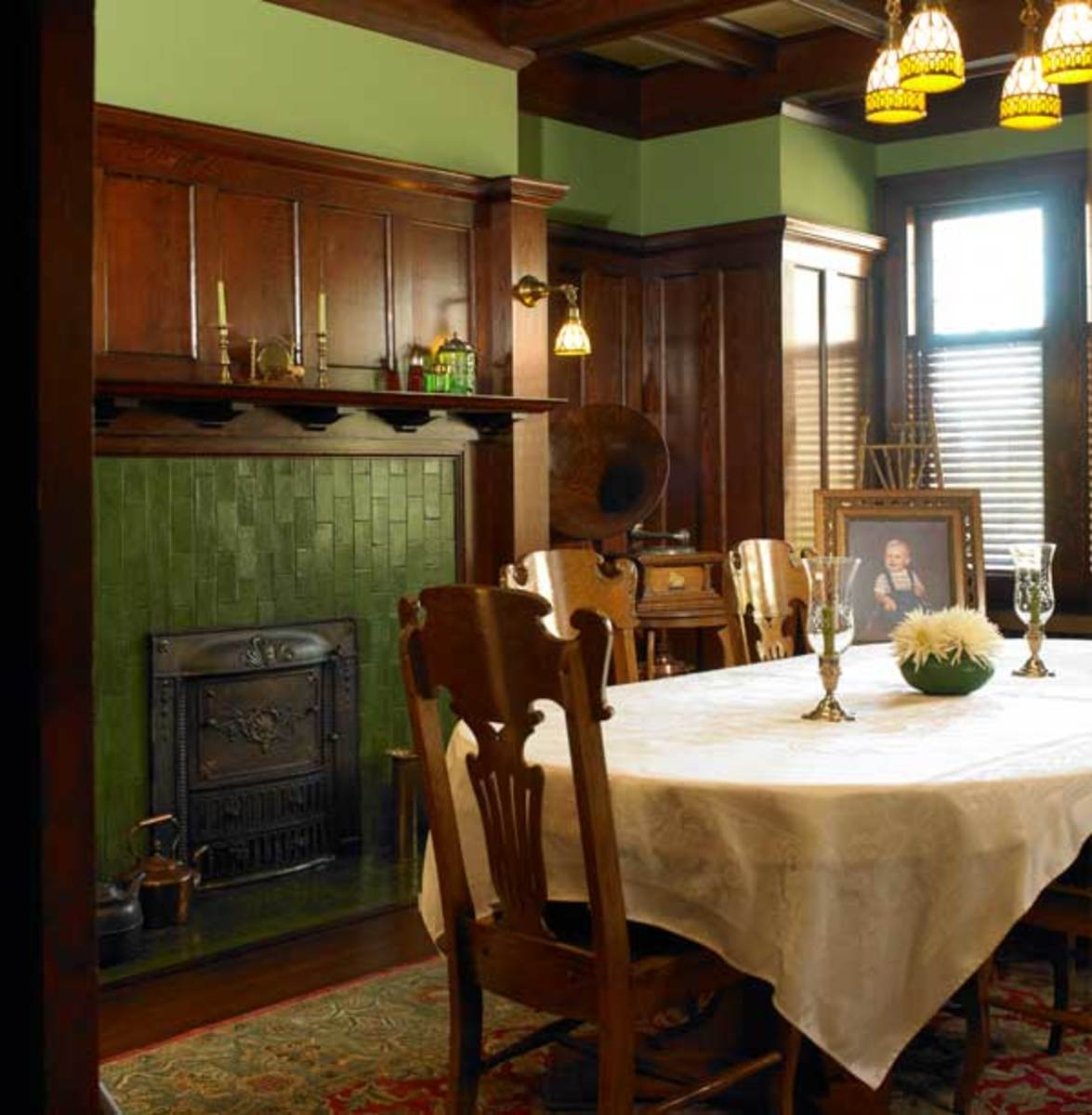 The dining room has a typically masculine look with a high wood wainscot and 'Butchart Green' walls cued by the original fireplace tiles.