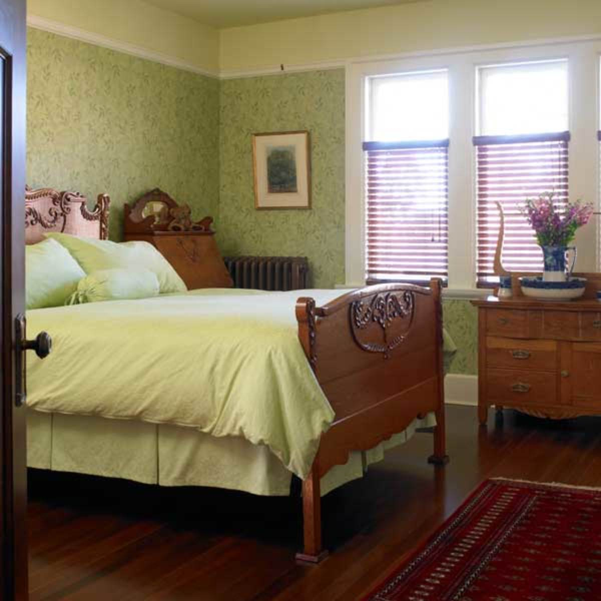 In the bedroom, wallpaper and carpet are historical reproductions; furniture is antique.