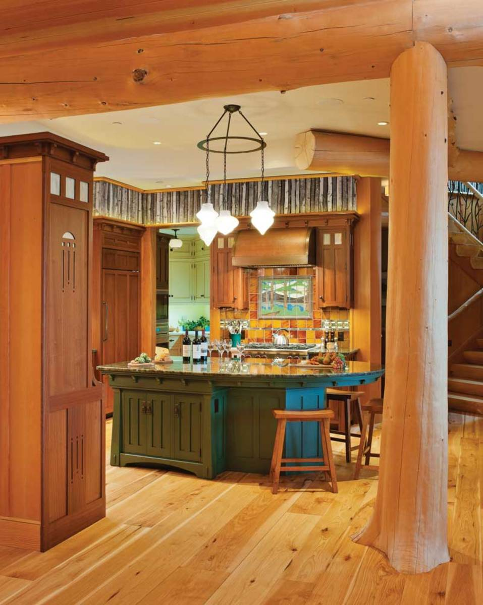 This artistic kitchen places furniture-quality cabinets in a room rustic with tree trunks and a twig frieze as a soffit. Arts & Crafts highlights include the Motawi tile mural and abstract cutouts. Photo: Jeffrey Stowell