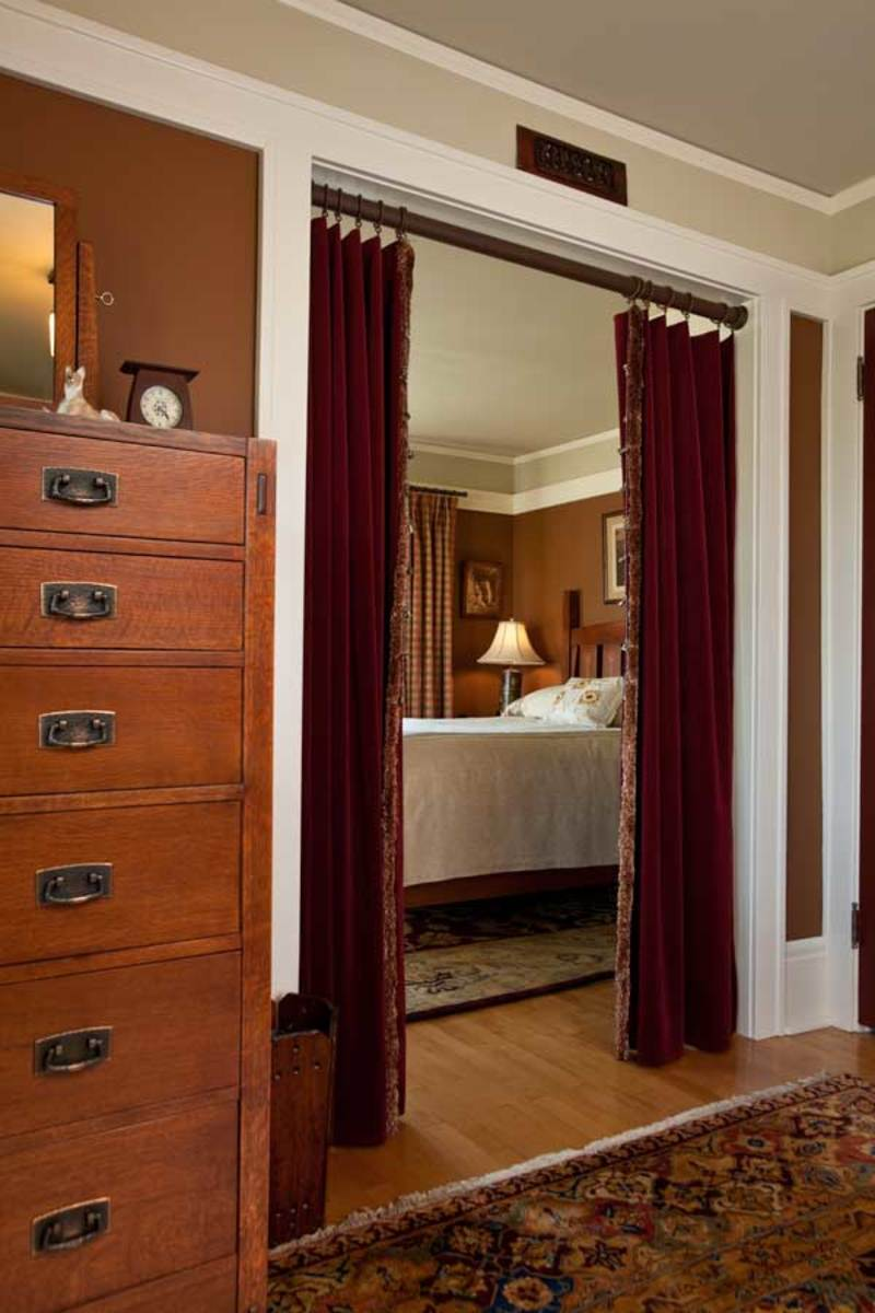 Vintage velvet portieres from the view from the dressing room into the bedroom. Bed and tall dresser are re-issued pieces by Stickley.