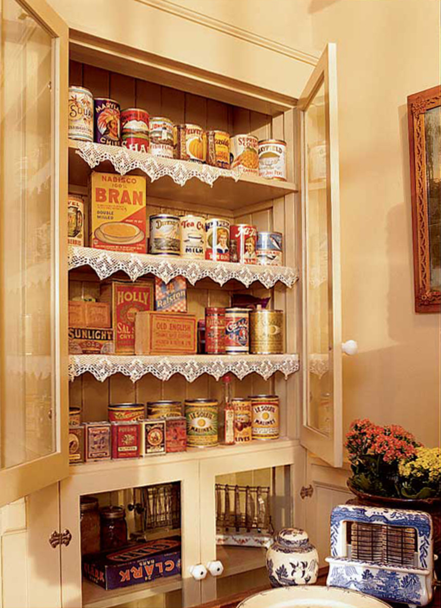 A former broom closet became a glass-door pantry cabinet, with old glass found in the house. The owners pasted their unused period canning labels to standard, turn-of-the-century-sized cans for display in front.