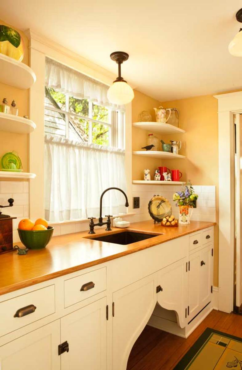 "In the pantry, wood countertops surround a copper sink. A dishwasher is hidden behind false drawer fronts. The ""flipper doors"" under the sink add a period touch."