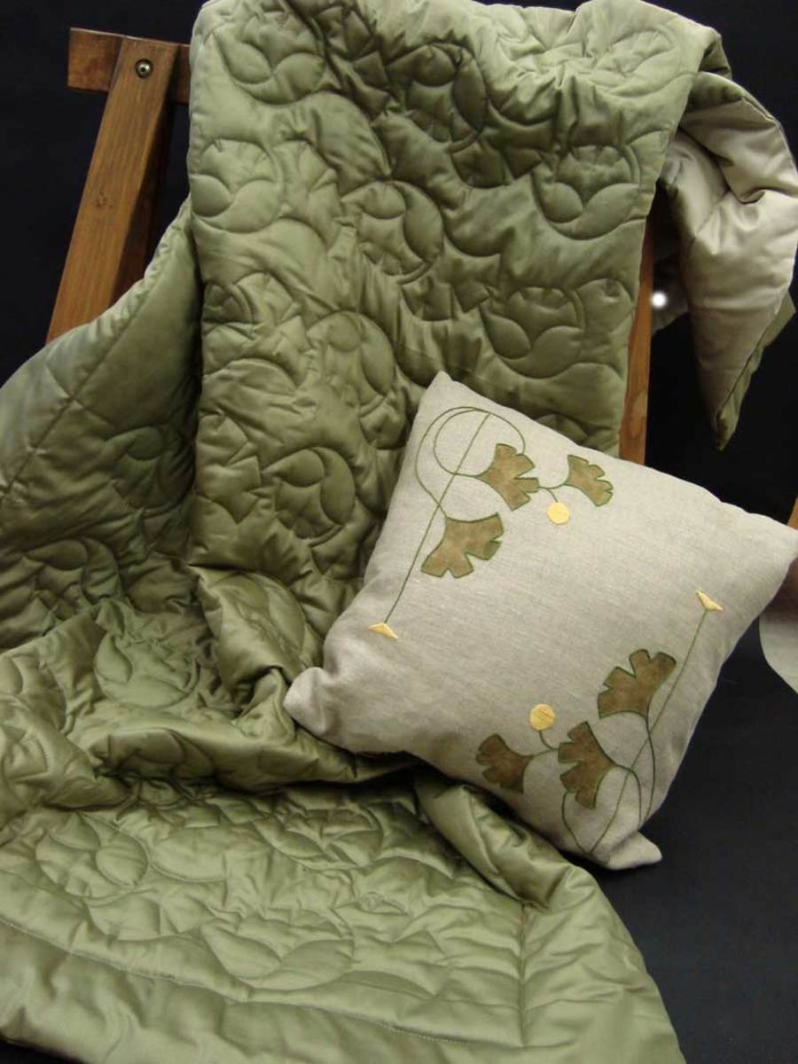A quilted comforter in sage polished cotton in the Ginkgo Border pattern, shown with an appliquéd and embroidered pillow.