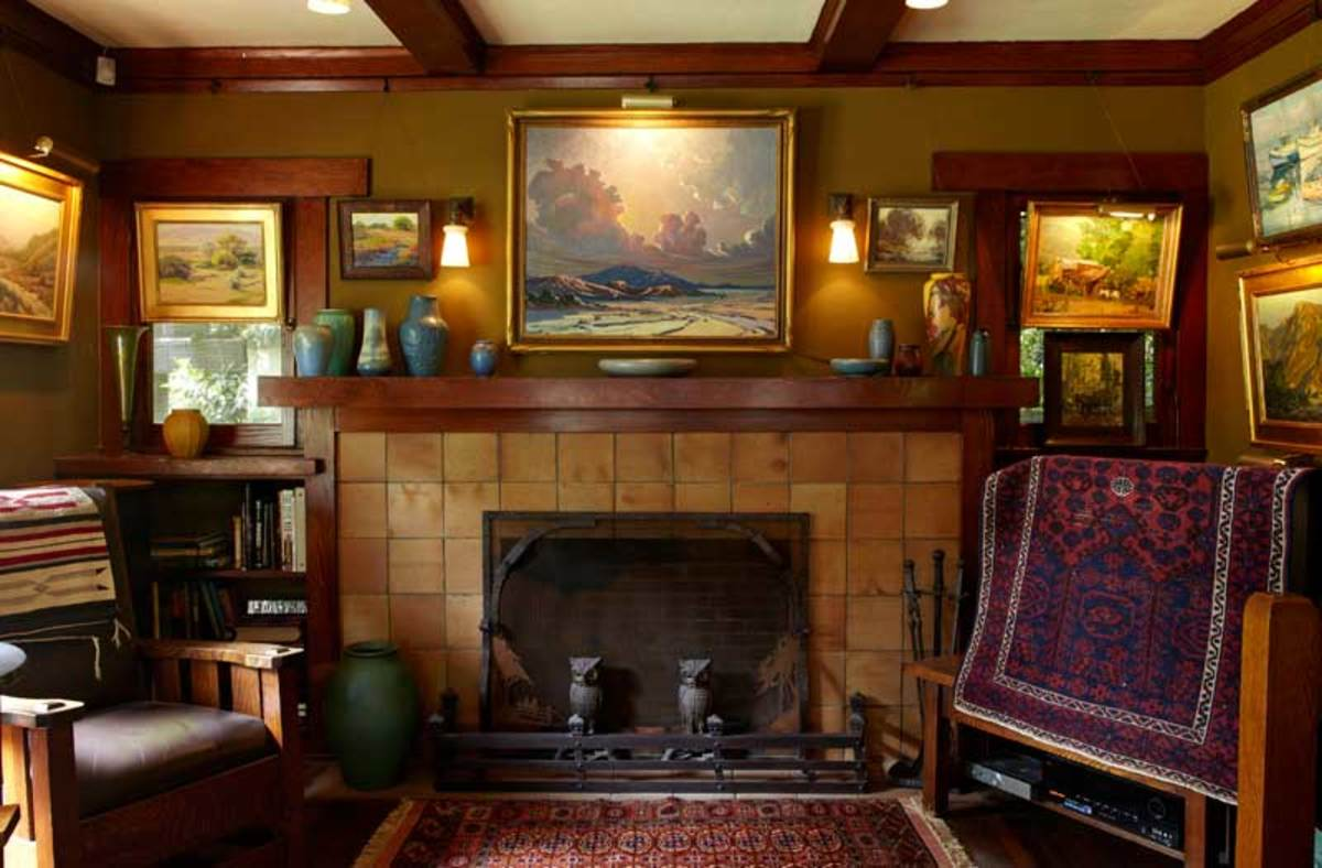 The fireplace (tile unknown) anchors a room rich with collections. Owl andirons are period; the chair is Limbert. The oil painting over the fireplace is by Howard Arden Edwards, 1937.