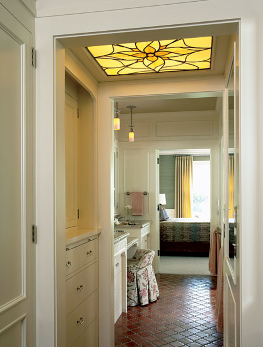 "Linking the bedroom to the bath by way of a ""master hall"" equipped with storage, sinks, and a vanity is an economical use of space in the retrofit of a 1913 historic building by David Heide Design Studio. Photo by Susan Gilmore."