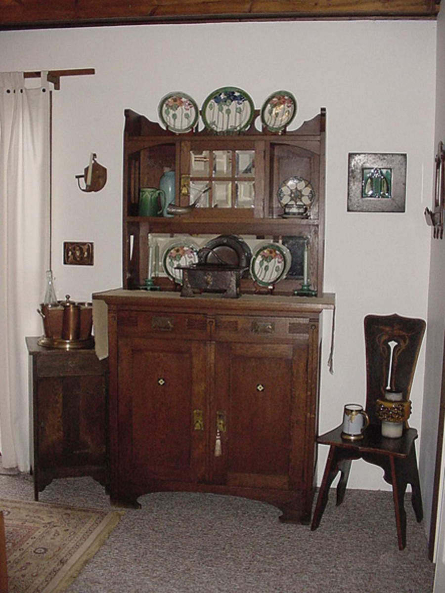 A European hutch displays Rookwood pots, Royal Douton 'Poppy' plates a Roycroft charger, and a fine hammered humidor.