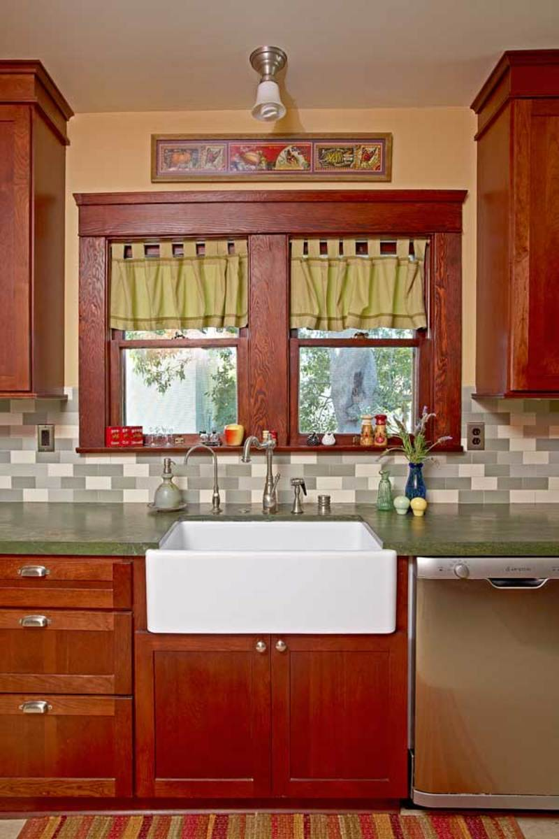 Green tiles and granite complement red trim and cabinets in the pleasantly old-fashioned kitchen.