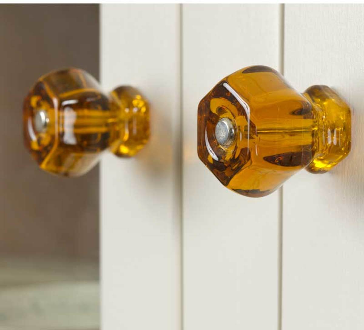 Cabinet knobs in amber glass add a warm glow to creamy white cabinets. Photo: Gridley + Graves
