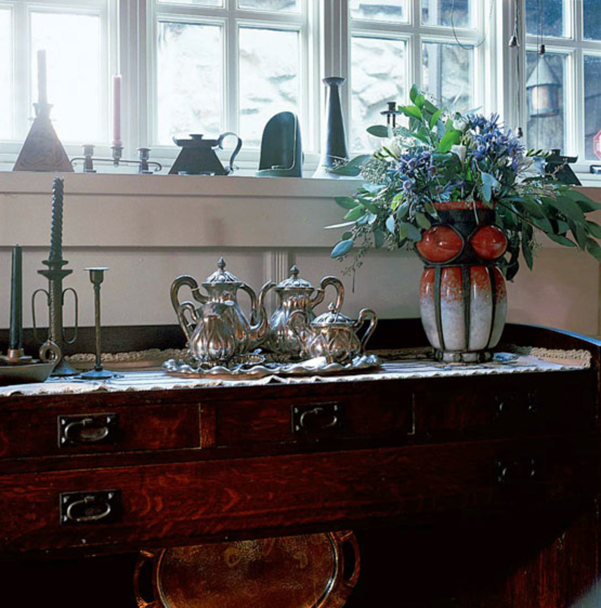 Part of the collection of single candlesticks sits on the sill; the silver service is a family heirloom.