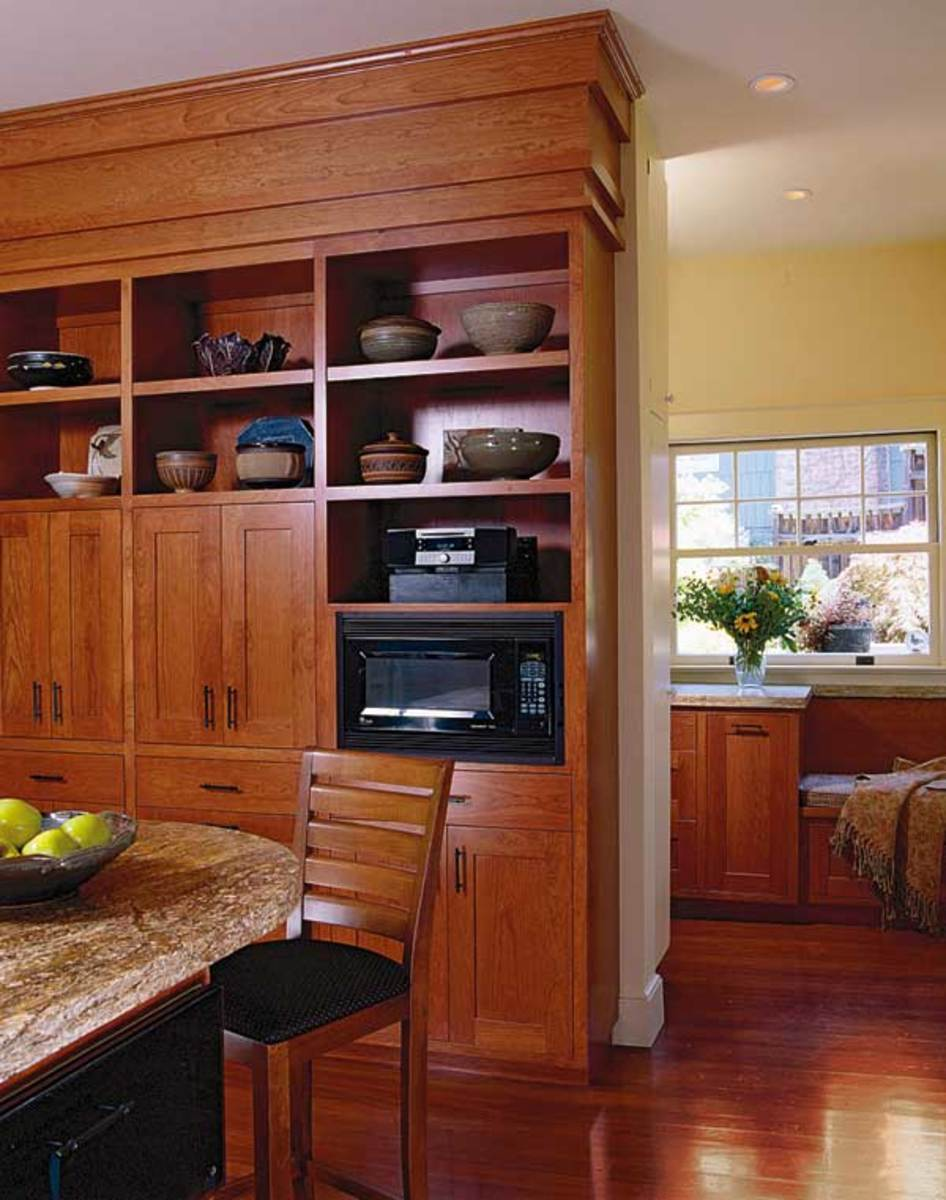 A wall of cherry cabinets provides a media center, storage, and open display for the pottery collection. Behind it is a spacious, well-lit entry hall that incorporates pantry storage.