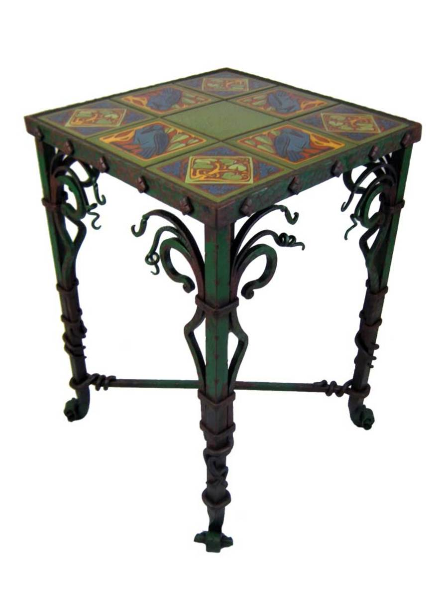 Hand-forged from the rivets and bars to the hammered border, the Raven table flaunts exuberant use of scrolls and tendrils. It is finished with new, hand-painted tiles in the style of Malibu Pottery.