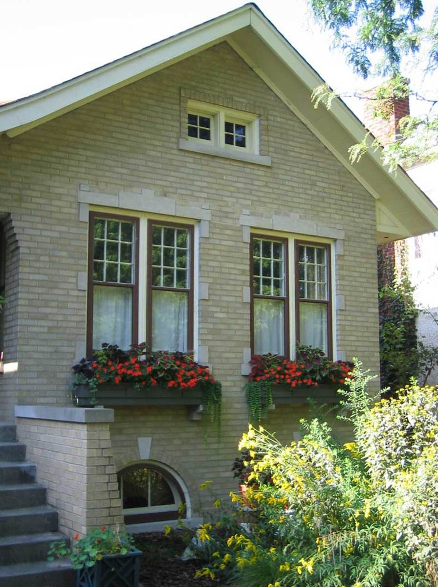 Replaced window boxes rest on two pairs of corbels, softening the façade of a gable-front brick house with limestone accents.