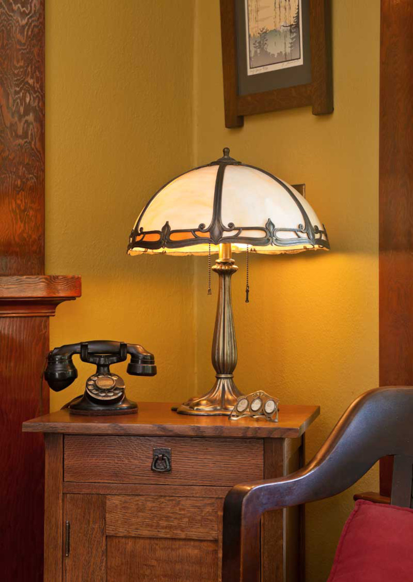 A vintage Bradley & Hubbard lamp and Denise's grandmother's telephone sit on a reproduction Stickley cabinet. The oak frame is from Alley Cat Arts in Portland.