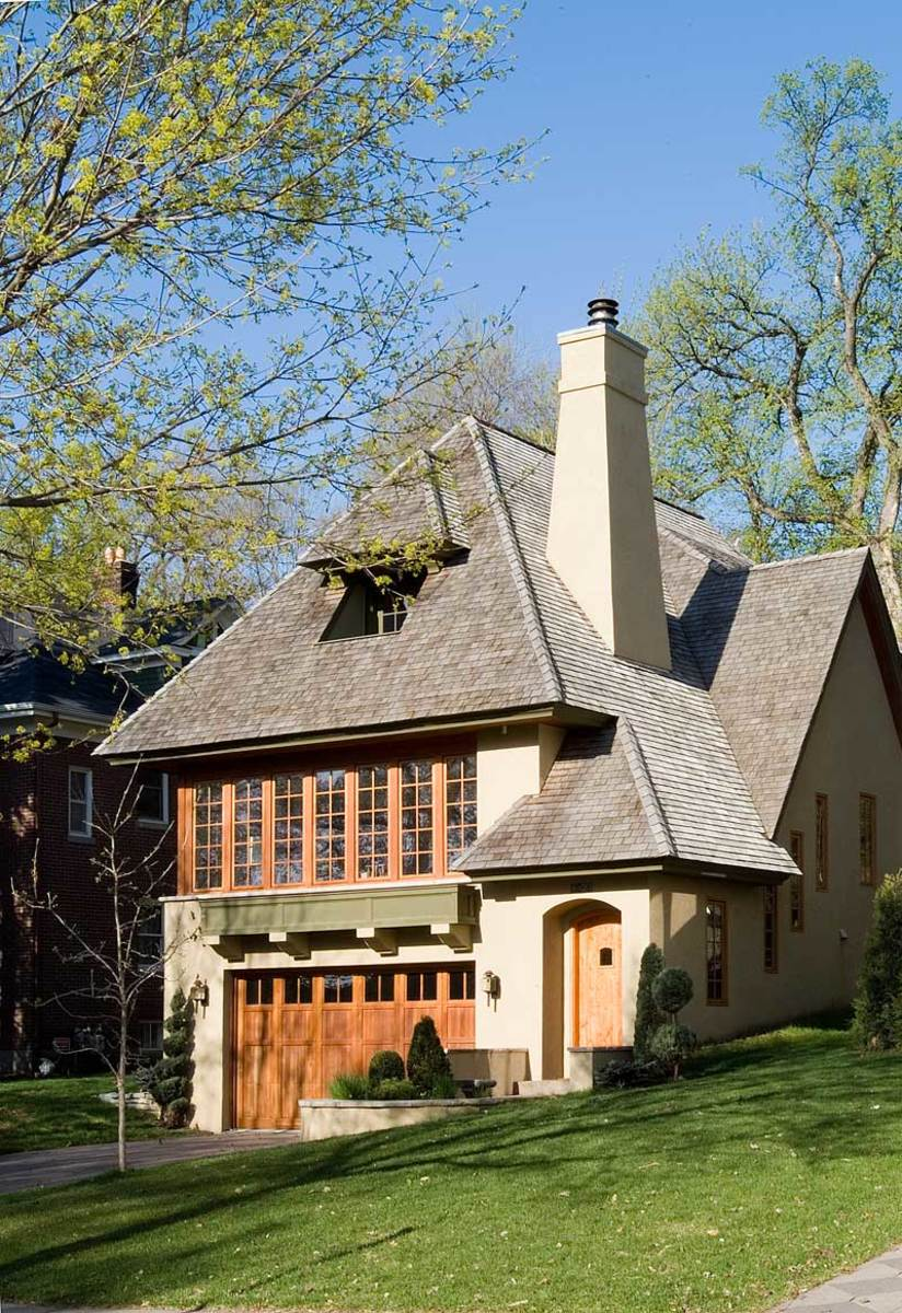 The garage tucks into the steep site, elevating living areas of a new English Arts & Crafts house designed to blend into the traditional neighborhood. Note the large window box held on corbels. Design by TEA2 Architects, Minnetonka, Minn.