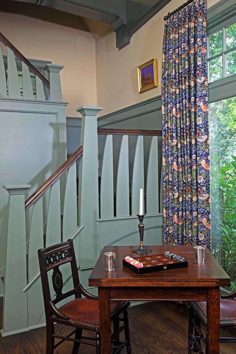 This spot, adjacent to the staircase up to the library, is an inviting place to play cards or board games. The drapery fabric is Morris's 'Strawberry Thief.'