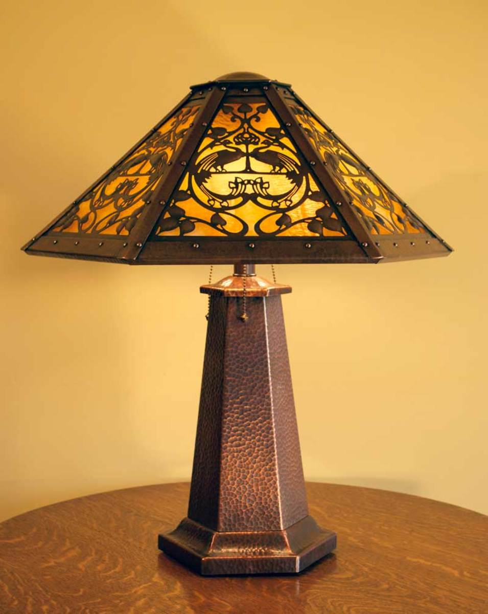 The hand-hammered six-sided Peacock lamp is a masterful tour-de-force. Also six-sided, the shade has a hammered, riveted frame, a three-dimensional domed cap, and hand-cut repoussé leaves and birds.
