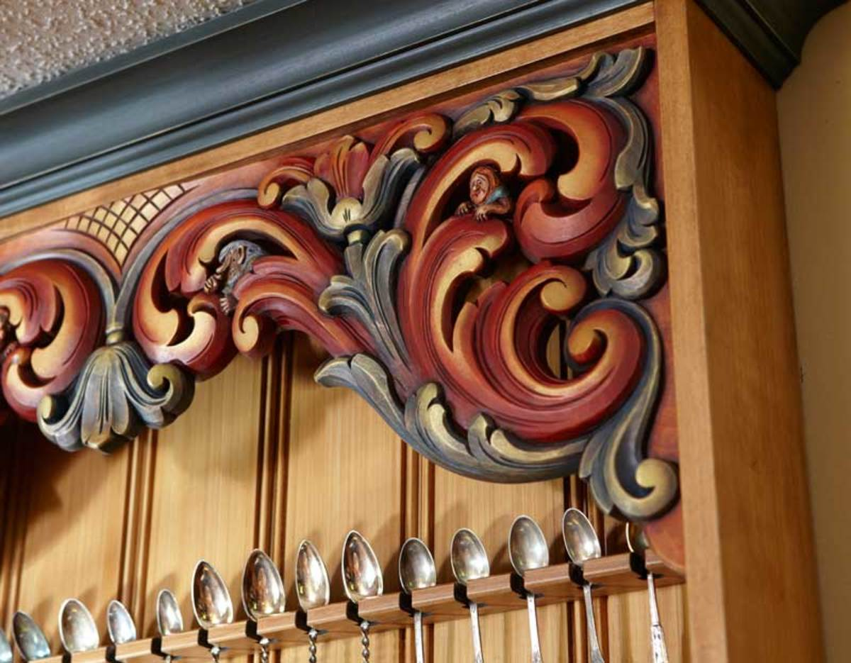 Troll-like caricatures peek around the scrollwork in the hand-carved Norwegian cabinet made by Hans Sandom, which holds 200 collectible spoons.