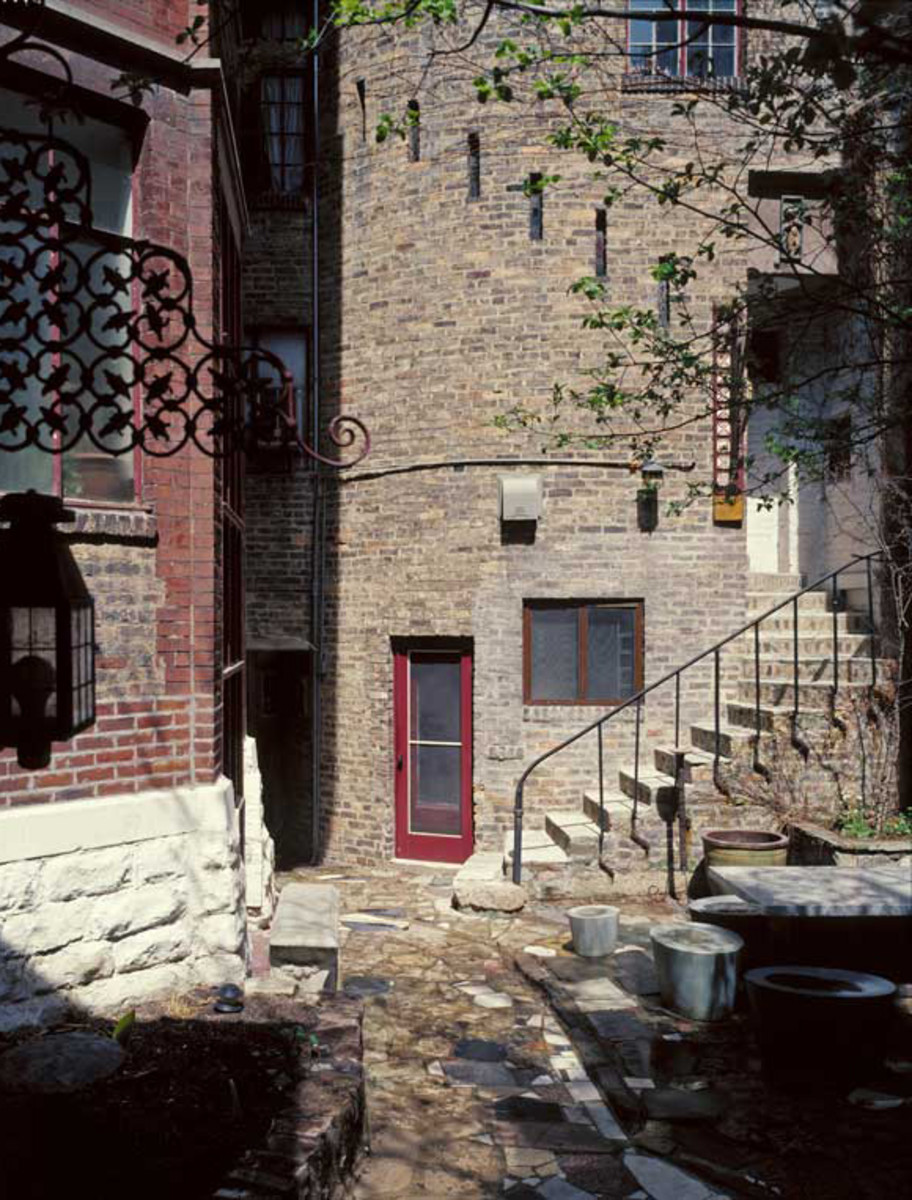 The Victorian house was subsumed in a brick façade; exterior stairways connect studios through courtyards.