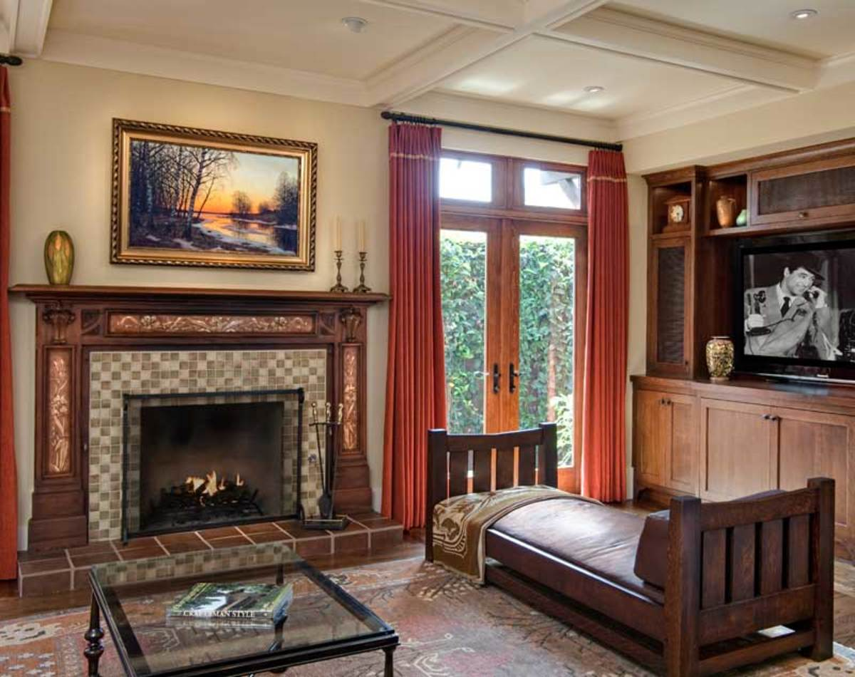 the family room is a frankly new space painted ceiling beams echo those in other rooms the english arts crafts mantel is carved mahogany with inset tile