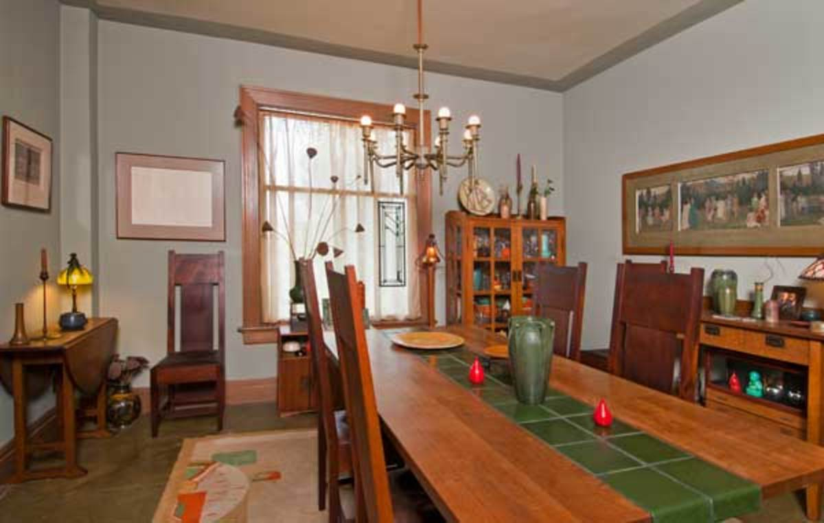 """The dining table is a commissioned replica of a Mission table Marrin found for $90, but with a """"runner"""" of salvaged Grueby tiles. The chandelier is antique."""