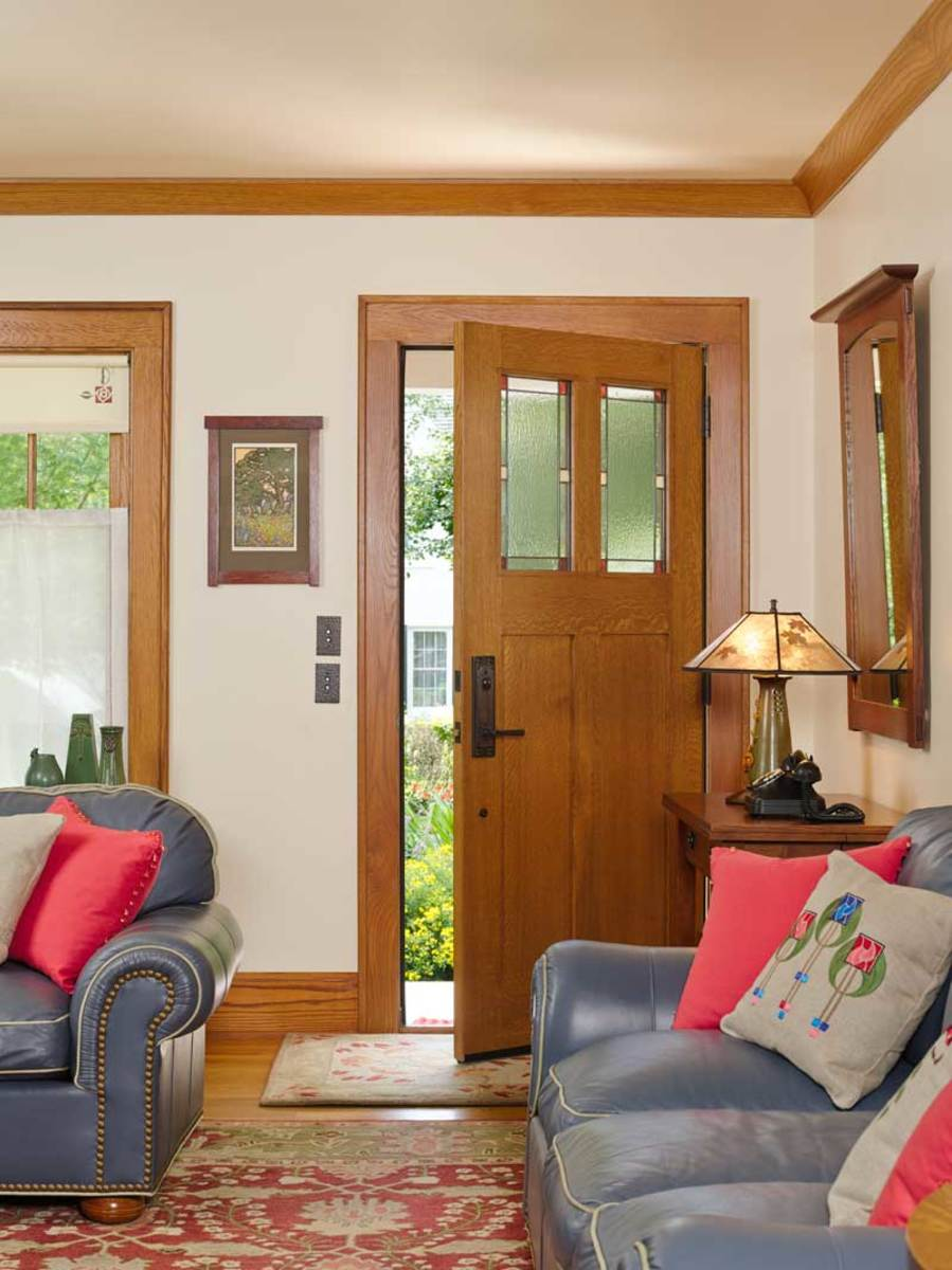 Opening directly into the living room, the more appropriate new door has leaded-glass panels set into quarter-sawn oak.