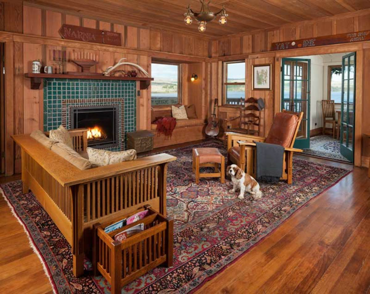 The living room is warmed by an expansive fireplace lined with custom Viridian green and Bark glazed Pewabic tiles accented with designs of local flora and fauna. The old interior walls were lightly sandblasted. The chandelier is original. The King Charles Spaniel is named D'Artagnan.