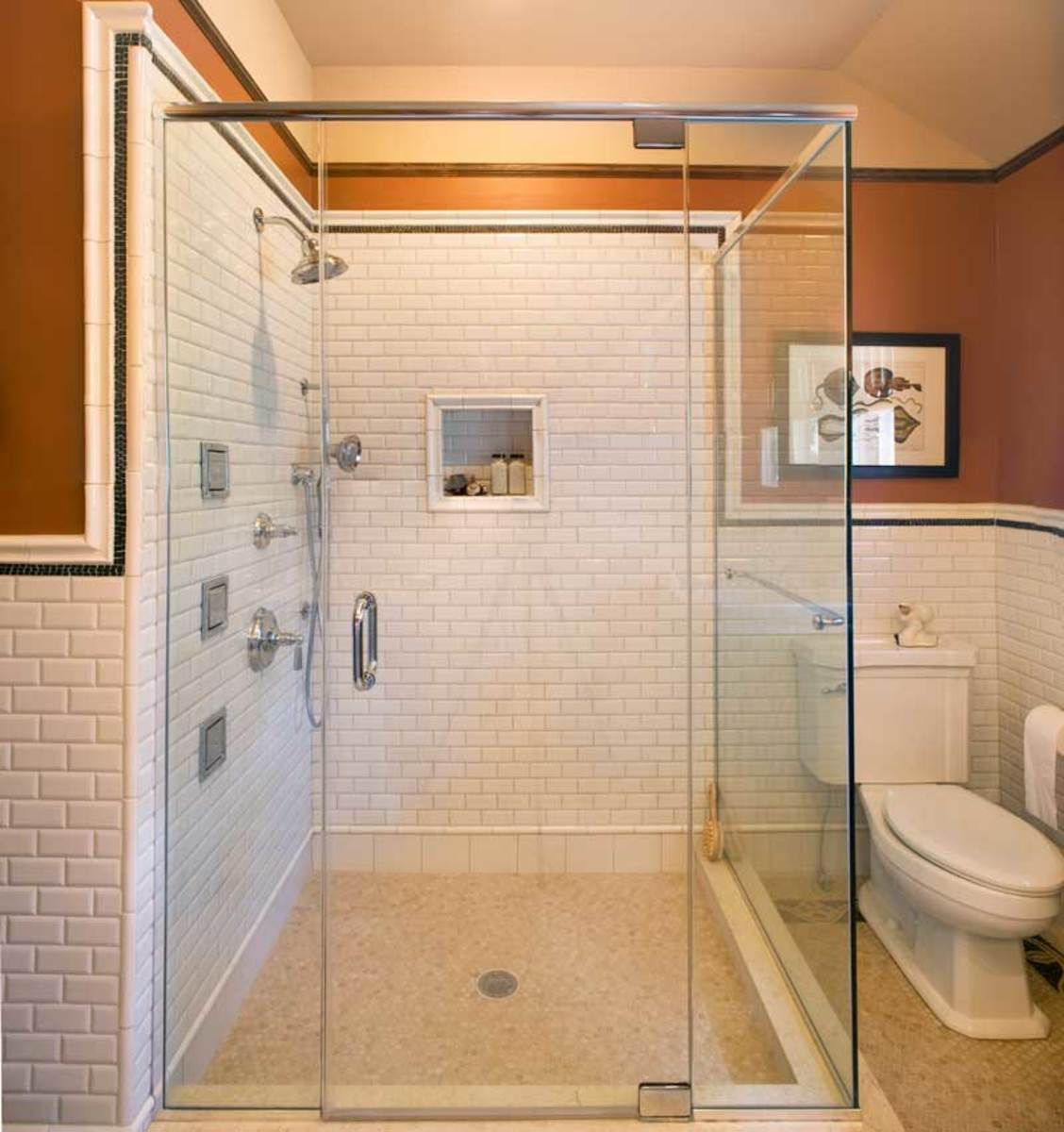 The shower is fully enclosed with glass panels, and has a custom niche for toiletries.