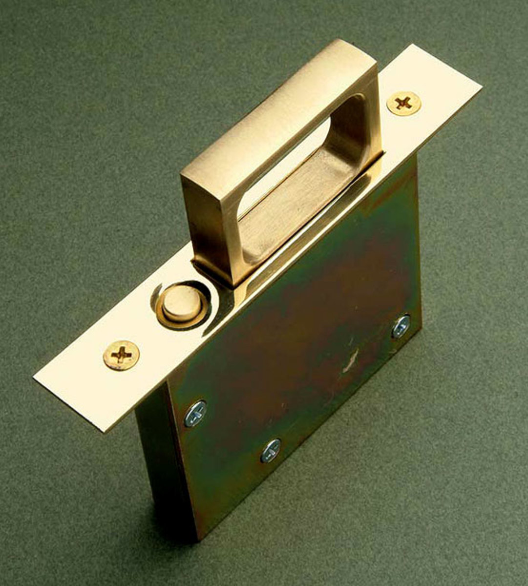 Mortised into the edge of a pocket door, this flush plate becomes a brass pull when you push the recessed button. Courtesy Crown City Hardware