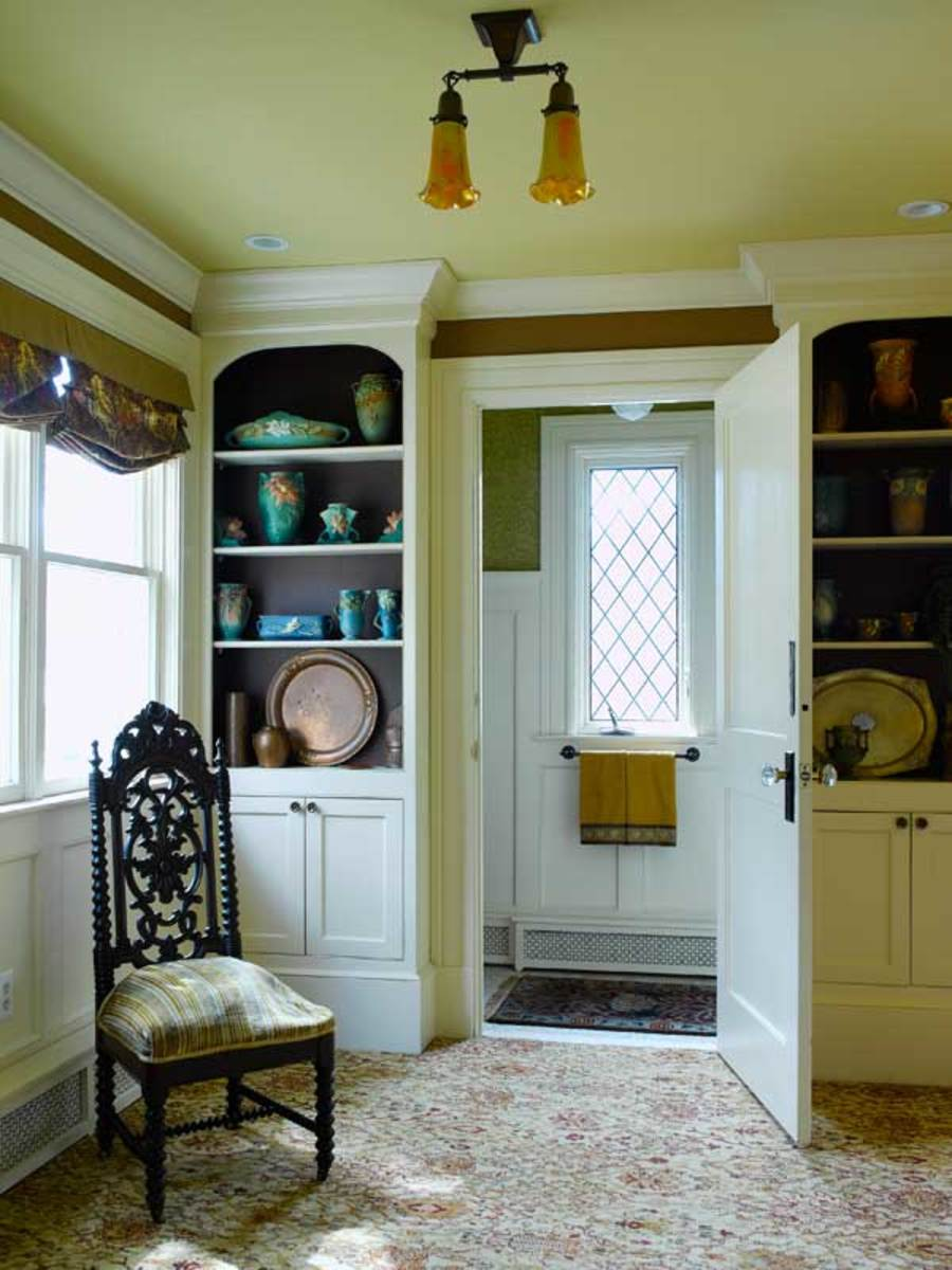 Floor-to-ceiling bookcases create a subtle buffer between the family room and the powder room beyond. The backs of the bookcases are painted the rich color 'Barista,' from Benjamin Moore, creating the impression of depth.
