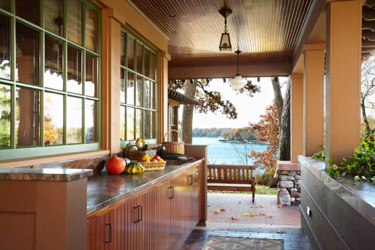 On the opposite  side of the kitchen, a new potting porch opens to a lake vista; it doubles as an outdoor kitchen along with a grill on the terrace.