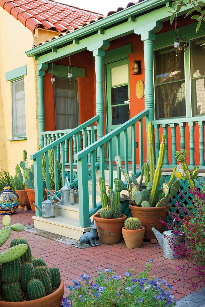 The exuberantly colored side porch opens onto a brick patio crowded with potted cacti.