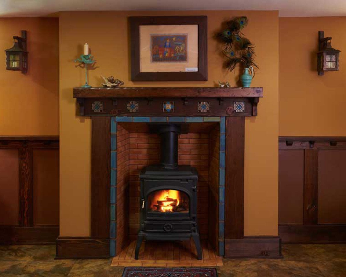 Art tiles surround a salvaged stove in the fireplace.