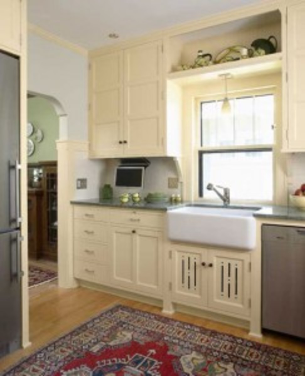 "Not all Revival kitchens are done in natural-finish hardwoods. This is a new interpretation of the ""sanitary"" white kitchen of the 1920s. Note the ""Prairie feet"" and the vented undersink door with decorative cut-outs. Design by David Heide. Photo by Susan Gilmore."