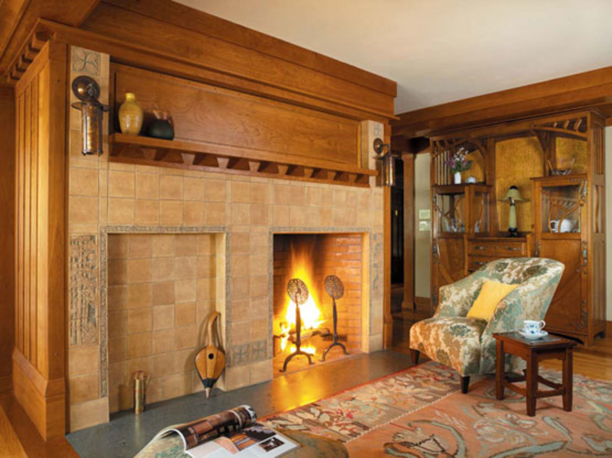 A massive hearth is the core of the house; this side is faced with new tiles in the style of Ernest Batchelder. The cabinet is an Austrian Art Nouveau antique. The corbelled mantel was developed from sketches the architect had done years ago in a study of a 1910 house.