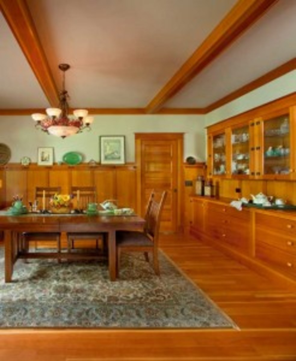 Typical of Craftsman-era dining rooms, a high wainscot with battens, brackets, and a plate rail accompanies a beamed ceiling and a built-in sideboard.