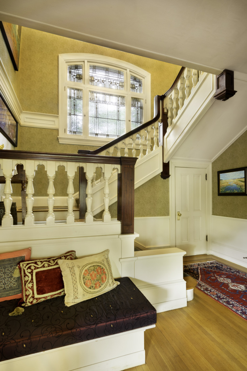 Honduras mahogany handrails, a built-in bench, and painted balusters distinguish the central stair. The original Povey Bros. window has Arts & Crafts style. The paper is Bradbury's 'Marigold'.