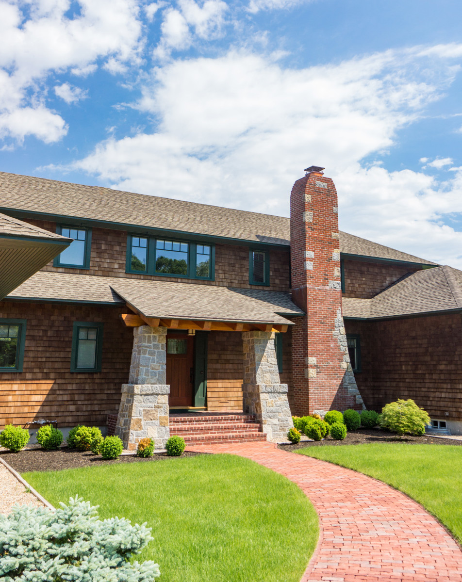 The main entry is on the façade that faces the approach to the house. Earthy building materials include more Rockport granite, along with traditional red brick and cedar shingles.