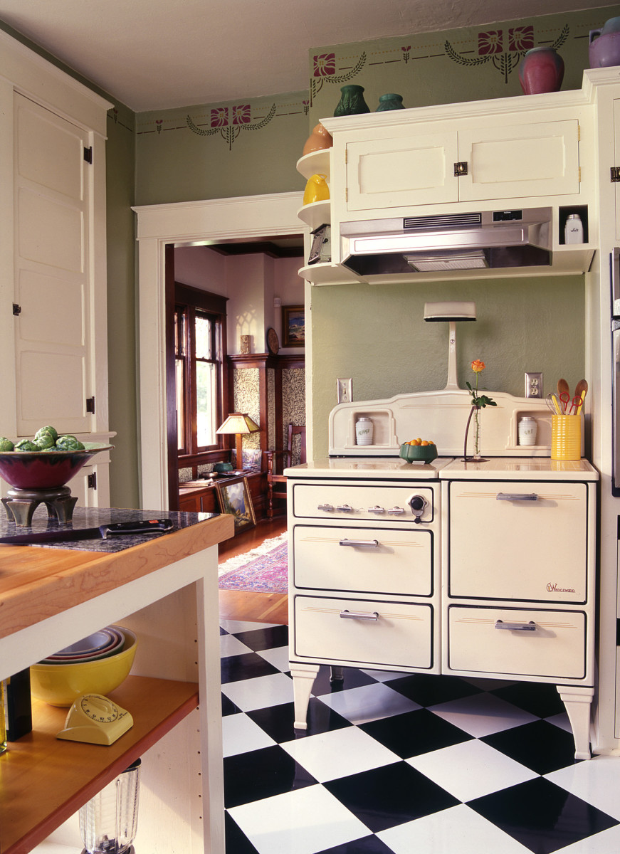 The 1930s Wedgewood gas stove features salt and pepper niches, burner covers, and a lamp. The dining room beyond has its original Douglas fir built-ins and wainscot.
