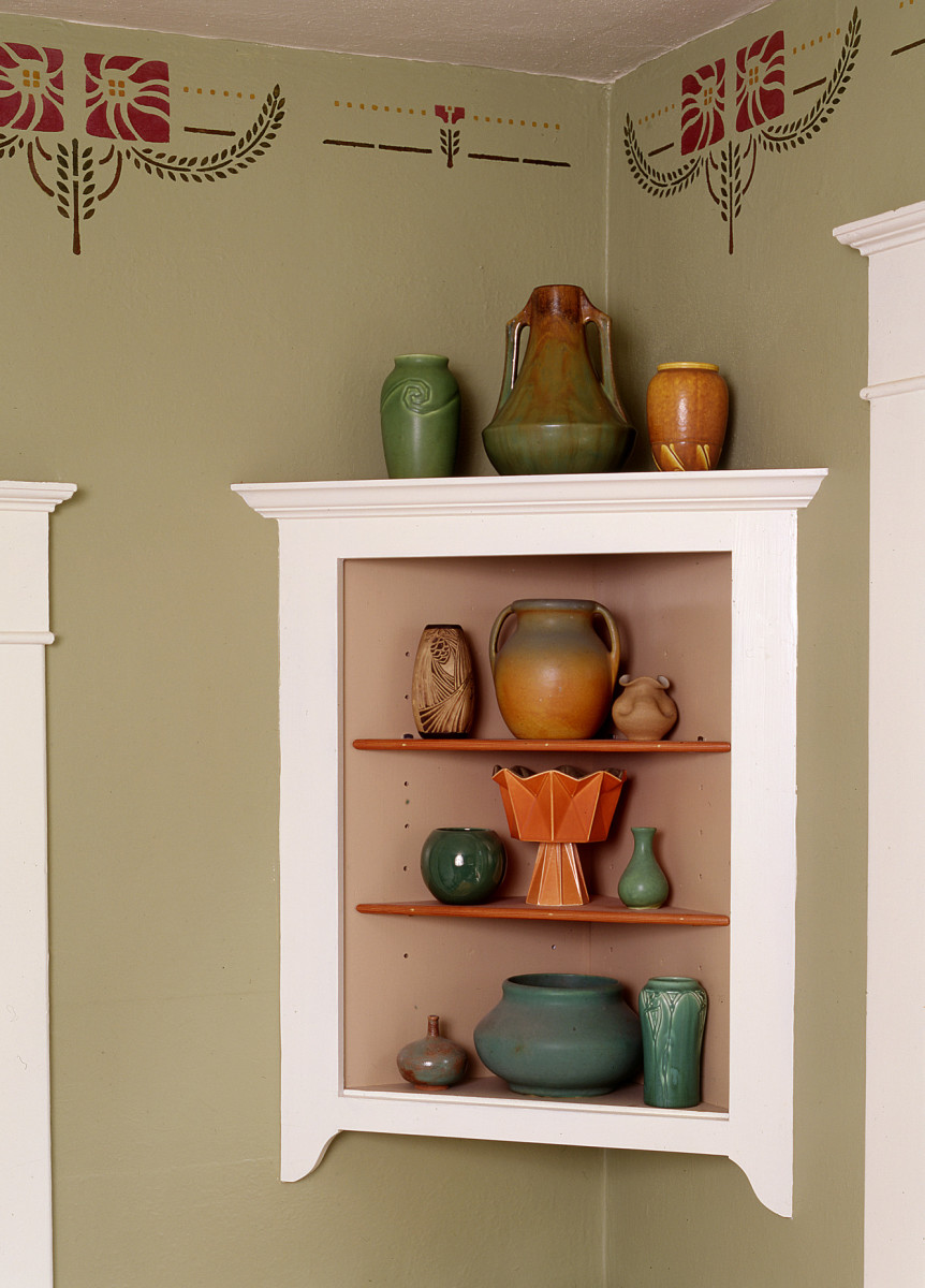 The owner built the hanging corner cupboard, picking up details from window and door trim. The painted interior showcases Rookwood, Weller, and Muncie pots and a Red Wing Prismatique piece at the center.