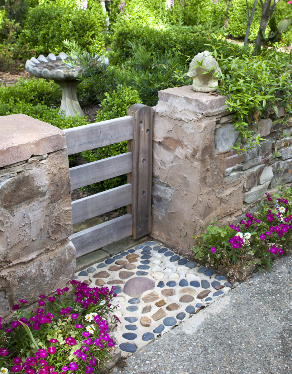 Smooth river stones were set in a decorative pattern in front of a gate made of cedar wood.